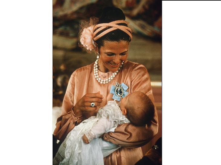 Königin Silvia hält ihren Sohn Prinz Carl Philip bei seiner Taufe auf dem Arm.