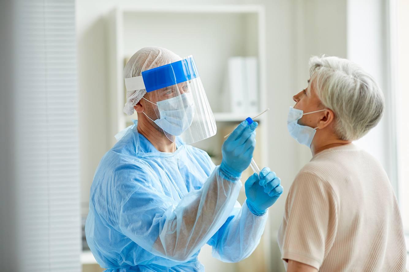Eine ältere Dame wird von einem Mediziner auf Corona getestet.