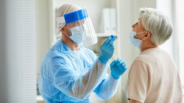 Eine ältere Dame wird von einem Mediziner auf Corona getestet. - Foto: iStock / SeventyFour