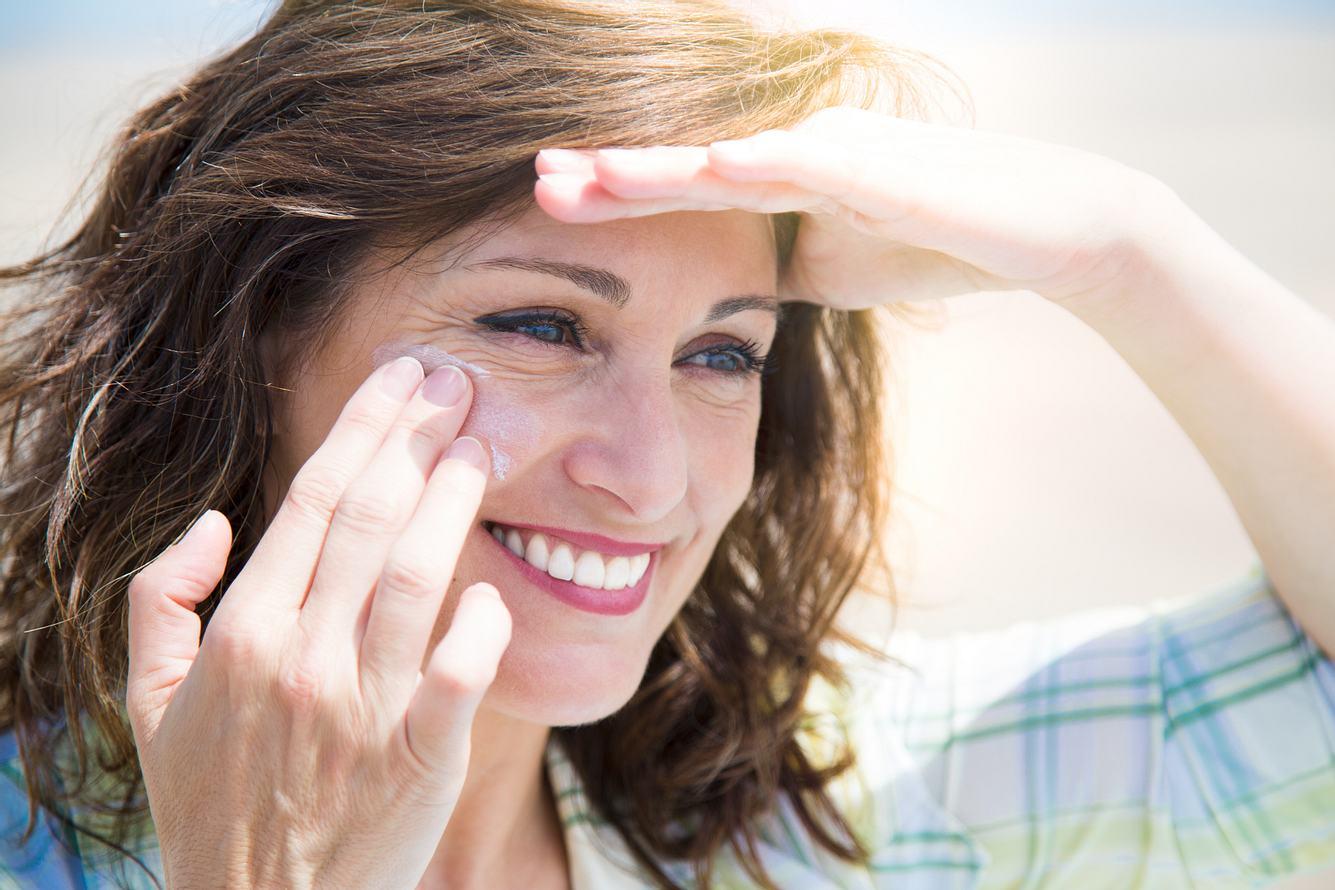 Frau cremt sich mit Sonnencreme für das Gesicht ein.