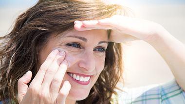 Frau cremt sich mit Sonnencreme für das Gesicht ein. - Foto: iStock/ ASIFE