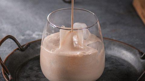 In eine Glas mit Eis wird Spekulatius-Likör eingeschenkt.  - Foto: Anna Makarenkova / iStock