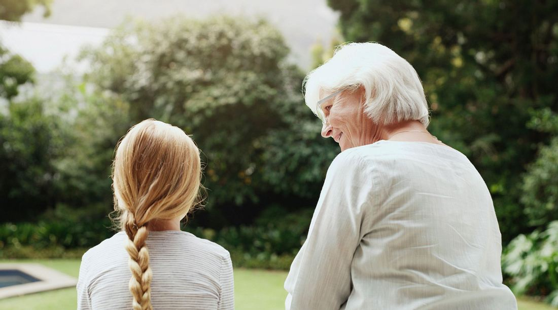 Oma und Enkelin sitzen im Garten.