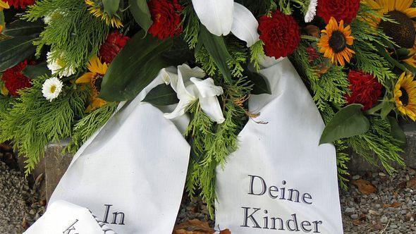 Trauerschleife mit Blumengesteck