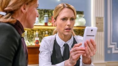 Rosalie schaut bei Sturm der Liebe entsetzt auf ihr Handy. - Foto: ARD/Christof Arnold
