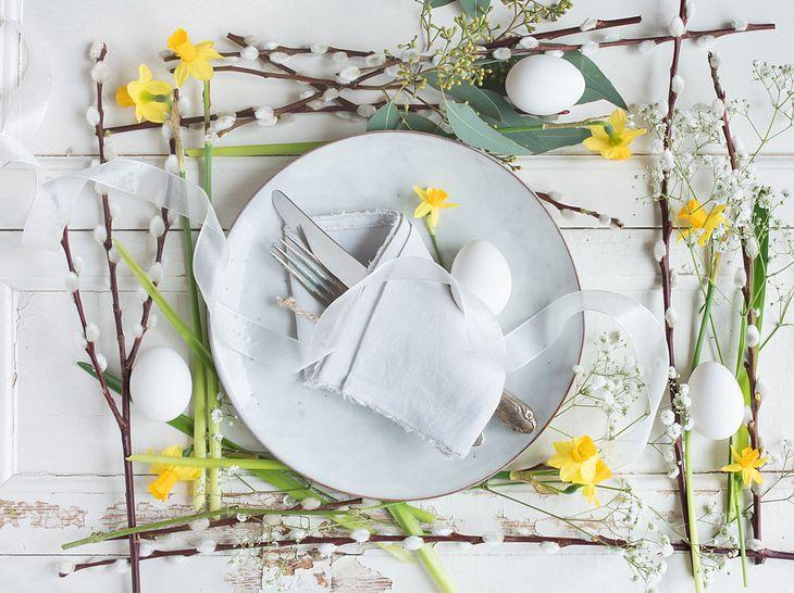 Tischdeko mit Narzissen und Ästen.