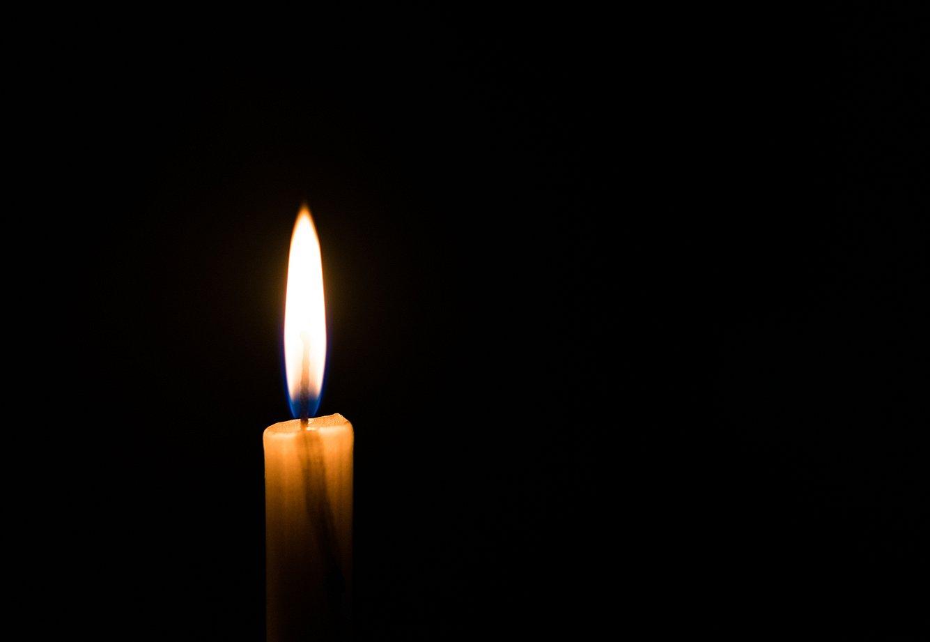 Eine brennende Kerze im Dunkeln.