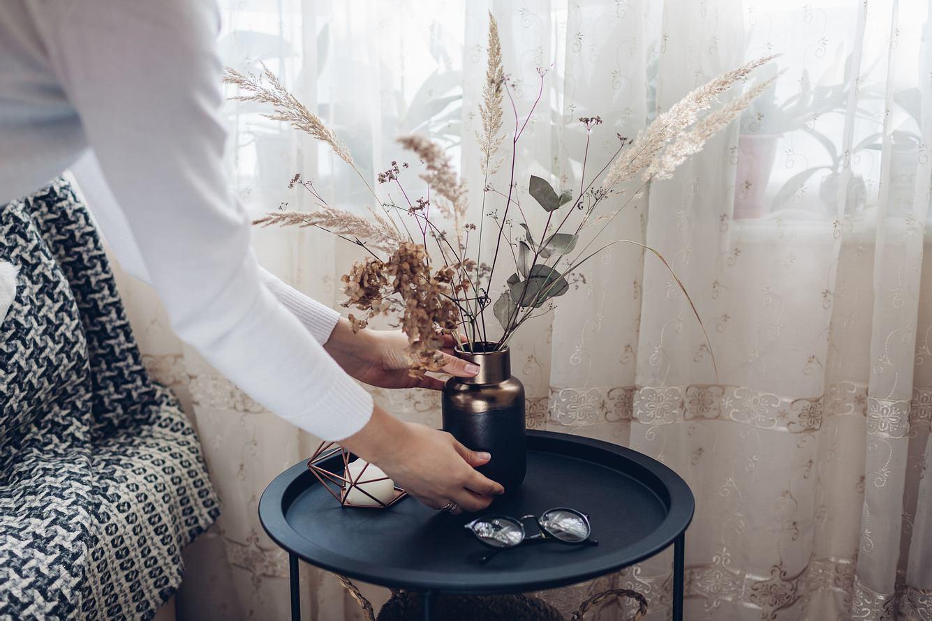 Frau stellt Trockenblumen Deko auf einen Tisch.