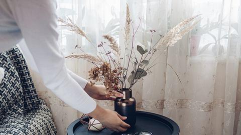 Frau stellt Trockenblumen Deko auf einen Tisch. - Foto: iStock/ Maryviolet