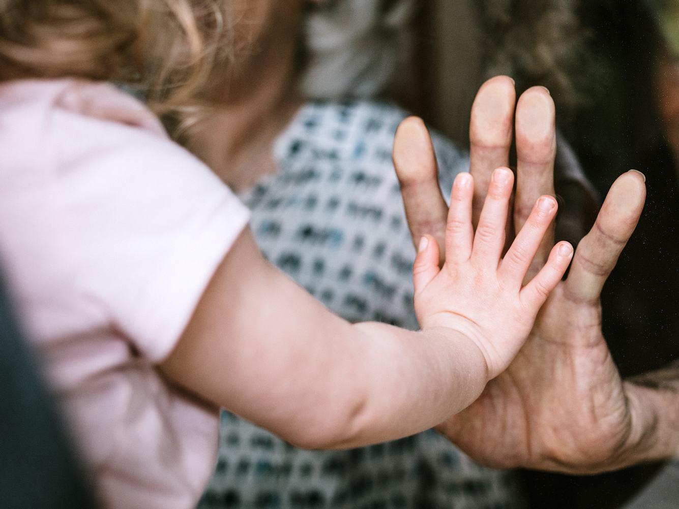 Kleines Mädchen drückt ihre Hand gegen eine Scheibe an Omas Hand.