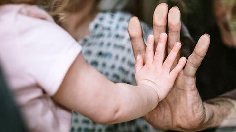 Kleines Mädchen drückt ihre Hand gegen eine Scheibe an Omas Hand. - Foto: RyanJLane / iStock