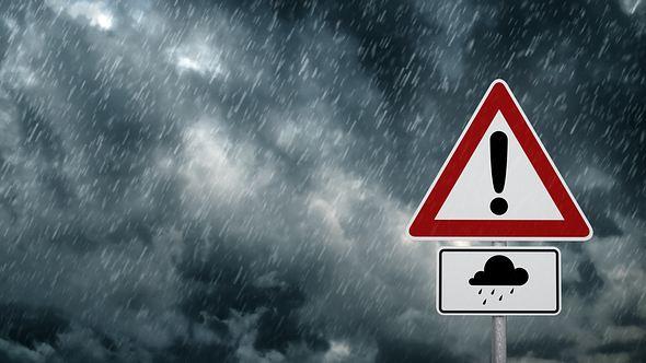 Ein Verkehrsschild warnt vor Unwettern. - Foto: iStock / trendobjects
