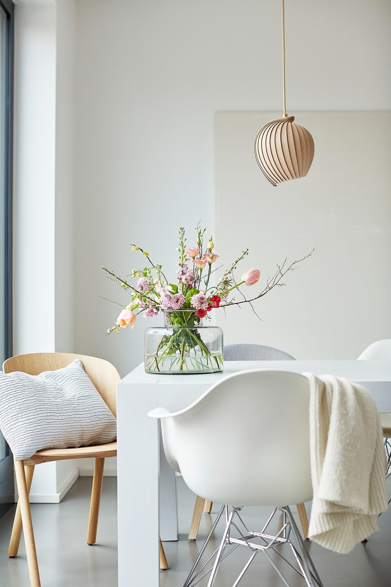 Vase befüllt mit Blumen steht auf einem Tisch.