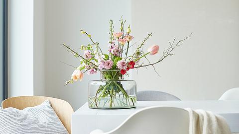 Vase befüllt mit Blumen steht auf einem Tisch. - Foto: iStock/2K Studio