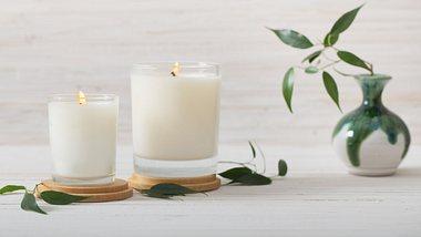 Vegane Kerzen in Weiß neben Vase - Foto: iStock/Maya23K