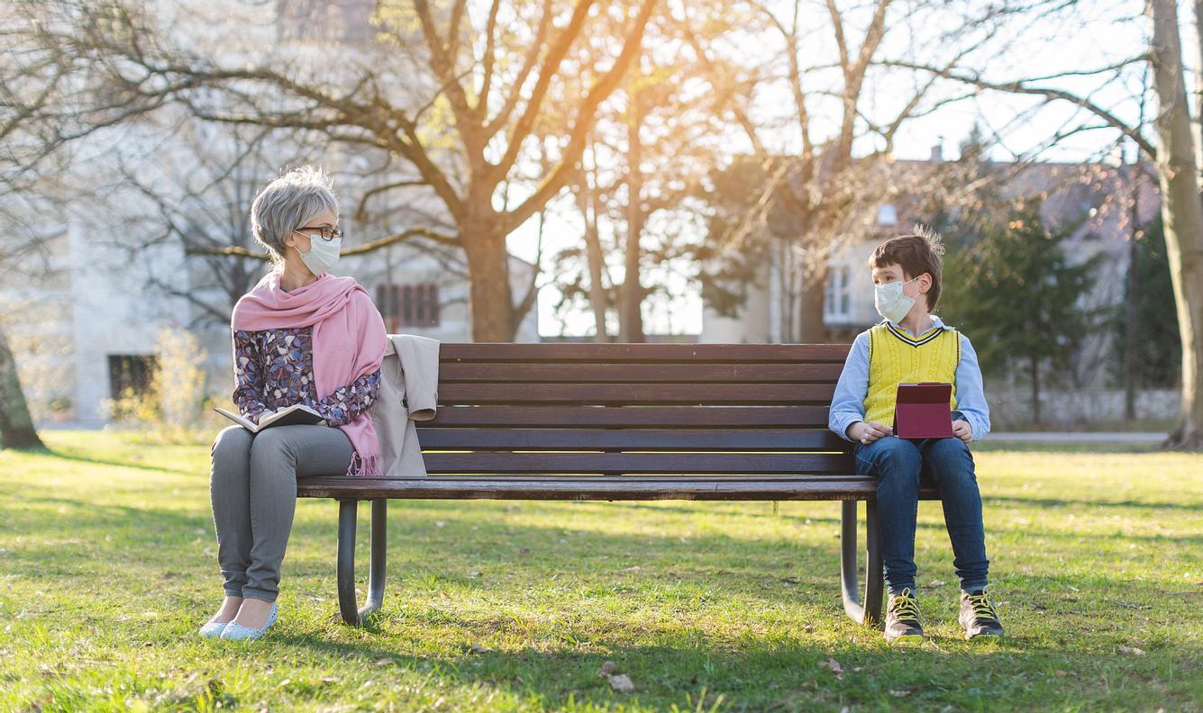 Eine Frau und ein Junge sitzen mit Abstand auf einer Parkbank.