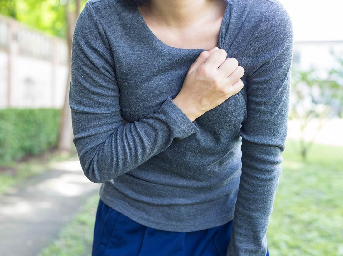 Frau hat Herzprobleme und fasst sich an die Brust