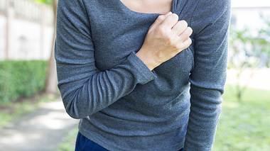 Frau hat Herzprobleme und fasst sich an die Brust - Foto: champja / iStock