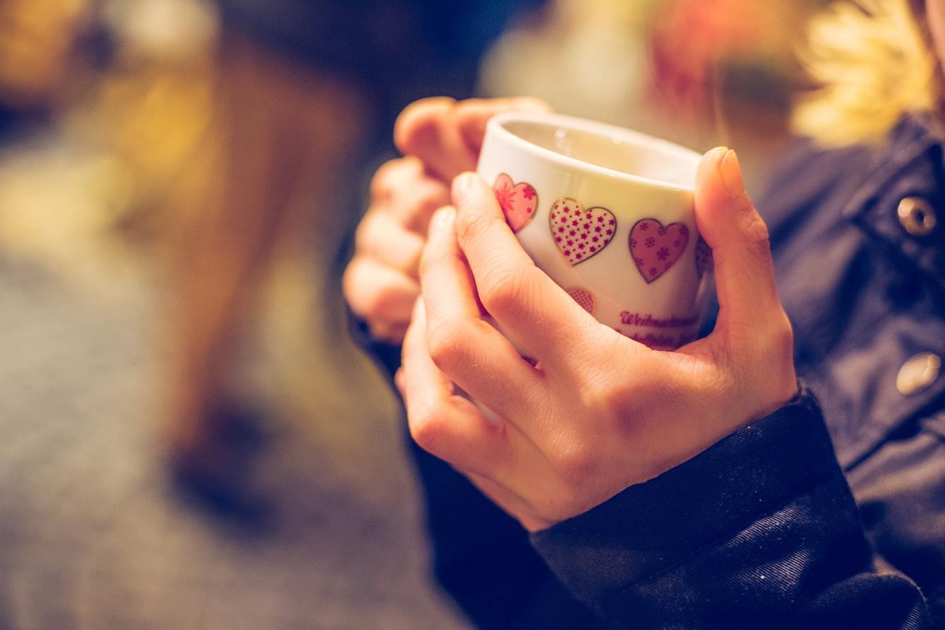Frau hält eine Tasse mit Glühwein in den Händen.