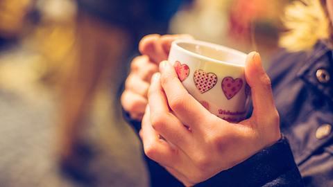 Frau hält eine Tasse mit Glühwein in den Händen.  - Foto: Patrick Daxenbichler / iStock