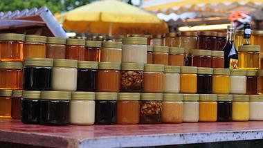 Verschiedene Honigsorten an einem Marktstand.