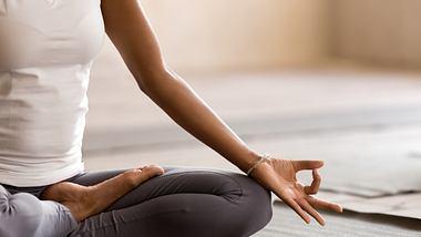 Frau macht Yoga zu Hause. - Foto: iStock/ fizkes
